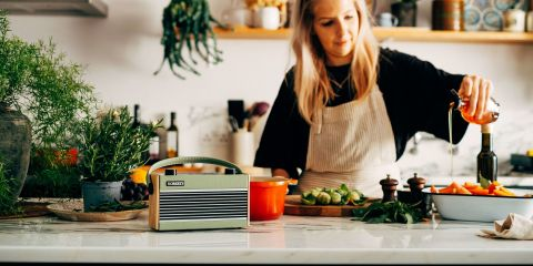 Woman cooking in kitchen listening to a Rambler BT in Green
